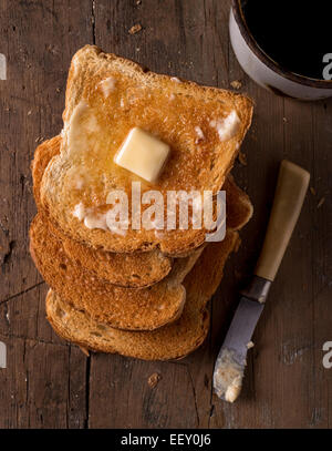Crusty buttered toast slices on a rustic tabletop with coffee. - Stock Photo