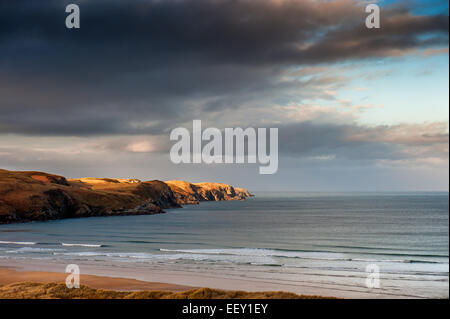 Looking across Strathy Bay to Strathy Point with strong Winter sun shining on the point - Stock Photo