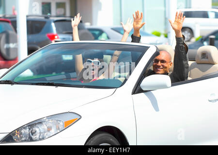 Couple leaving car dealership in convertible - Stock Photo