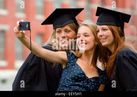 Three friends at graduation ceremony - Stock Photo