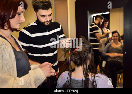 Young male and female trainee hairstylists working on braiding hair of a female customer in a salon - Stock Photo