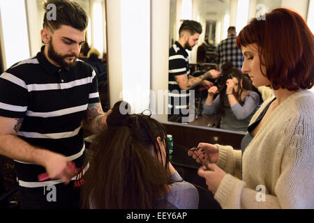 Young male and female trainee hairstylists working on a model in a salon with mirror - Stock Photo