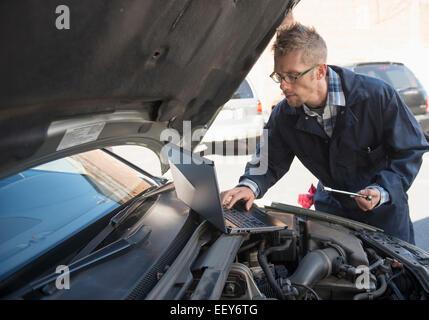 Mechanic using laptop while repairing car - Stock Photo
