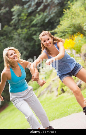 Two women inline skating at a park - Stock Photo