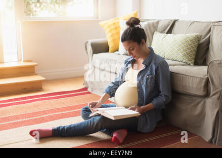 Pregnant woman sitting on floor reading book - Stock Photo