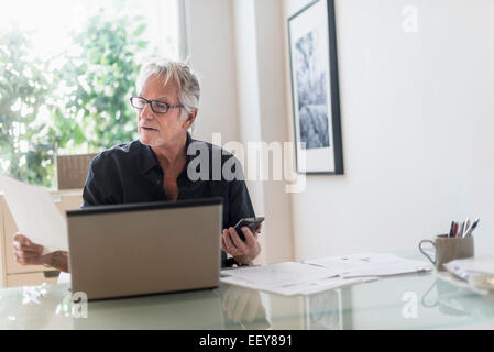 Senior man sitting in home office and using laptop - Stock Photo