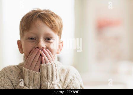 Portrait of boy (6-7) with hands covering mouth - Stock Photo