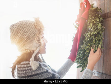 Side view of young woman hanging Christmas wreath on entrance door - Stock Photo