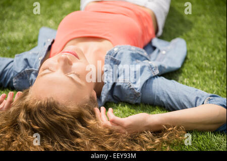 Young woman lying on lawn - Stock Photo
