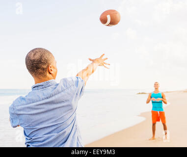 USA, Florida, Jupiter, Young men playing football on beach - Stock Photo