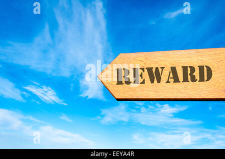 Wood arrow sign against clear blue sky with Reward message - Stock Photo