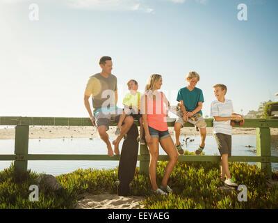 USA, California, Laguna Beach, Family with three children (6-7, 10-11, 14-15) talking on beach - Stock Photo