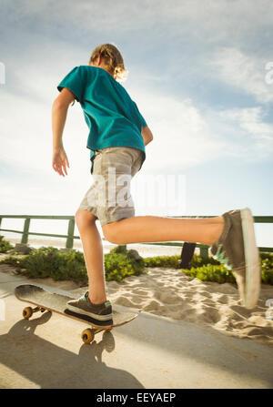 USA, California, Laguna Beach, Teenage boy (14-15) skateboarding on path on beach - Stock Photo