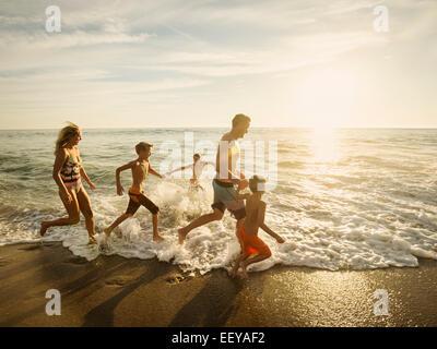 USA, California, Laguna Beach, Family with three children (6-7, 10-11, 14-15) running on beach - Stock Photo