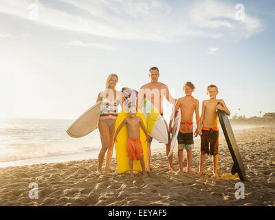 USA, California, Laguna Beach, Portrait of family with three children (6-7, 10-11, 14-15) with surfboards on beach - Stock Photo
