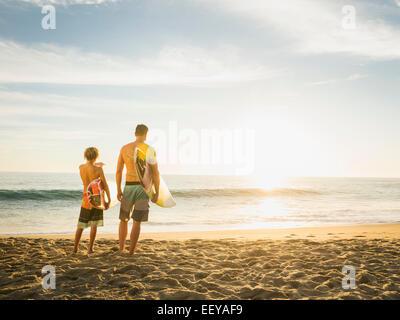 USA, California, Laguna Beach, Father and son (14-15) looking at sea - Stock Photo