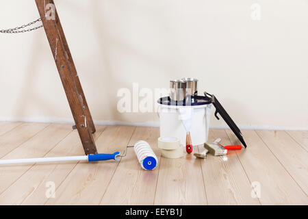 ... Painting supplies with ladder against a wall to be repainted - Stock  Photo