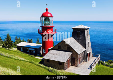Canada, Quebec, Pointe-a-la-Renommee lighthouse and houses against sea at sunny day - Stock Photo