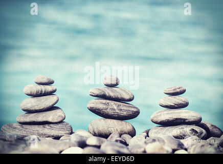 Vintage retro hipster style image of stones on beach, Zen spa concept background. - Stock Photo