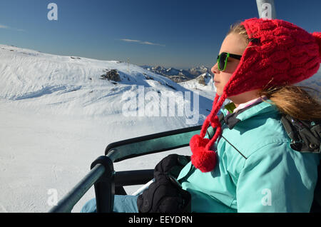 Young girl with red winter hat and  sun glasses on  chair lift at ski resort Pierre saint martin in Atlantic Pyrenees, - Stock Photo
