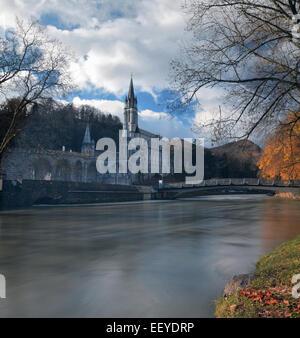Sanctuaries of Lourdes seen from Gave de Pau River. The bridge leading the major place of Roman Catholic pilgrimage - Stock Photo