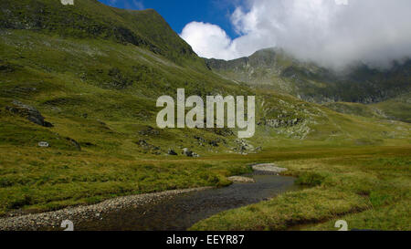 Mountain landscape with a river and clouds in the sky - Stock Photo