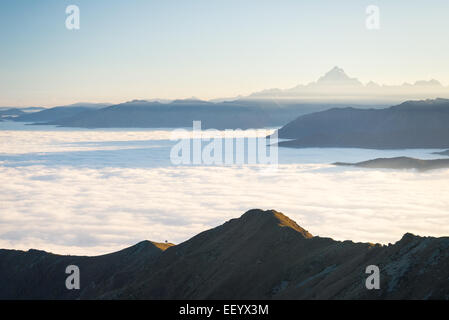 Stunning landscape at sunset on the italian western Alps with M. Viso peak in the background and clouds covering - Stock Photo
