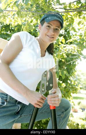Garten Frau Jung Laecheln Gluecklich Portrait Frauenportrait Sommer Gartenschere Astschere Gartengeraet Schirmmuetze - Stock Photo