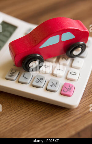 Red Toy Wooden Car On Calculator To Illustrate Cost Of Motoring - Stock Photo