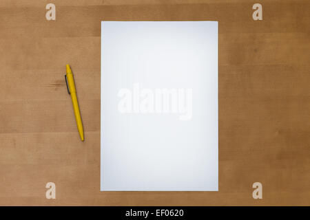 Pen and a blank white paper sheet on a wooden table surface, viewed from above - Stock Photo