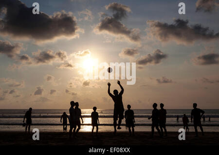 Young local boys playing football on a beach in Bali, Indonsesia - Stock Photo