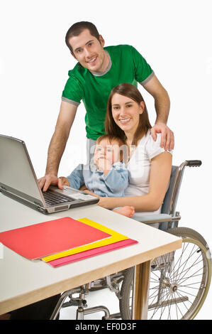 Parents and their baby sitting at laptop - Stock Photo
