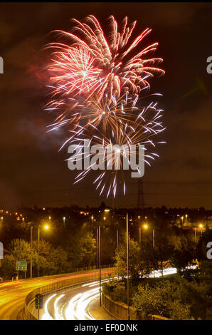 Firework display on November 5th with the streaked lights of cars on the A12 road underneath - Stock Photo
