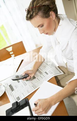 Frau Tageszeitung Stellenanzeigen Markieren Telefonieren Arbeitssuche Arbeitslos Arbeitslosigkeit Jobsuche Zeitung - Stock Photo