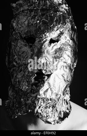 Portrait of a man dressed in scary masks foil - Stock Photo