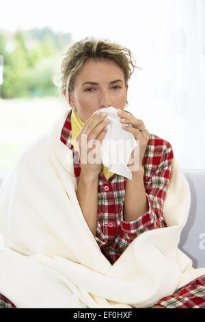 Frau Jung Schnupfen Taschentuch Erkaeltung Krank Krankheit Grippe Grippeerkranknung Nase Putzen Gesicht Viruserkrankung - Stock Photo