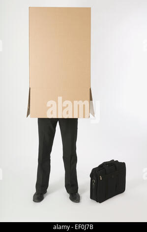 Businessman with a cardboard box over his head - Stock Photo