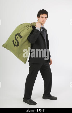 Businessman carrying a bag of money over his shoulder - Stock Photo