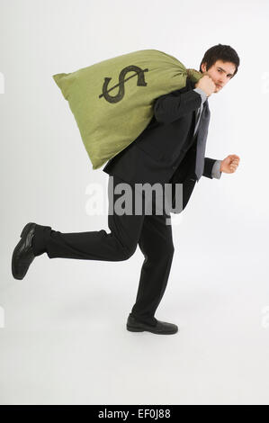 Businessman running with a bag of money over his shoulder - Stock Photo
