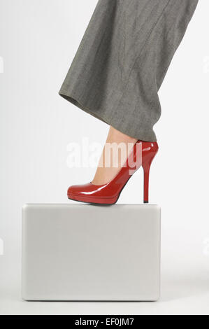Woman's foot in red high heeled shoe on top of laptop - Stock Photo