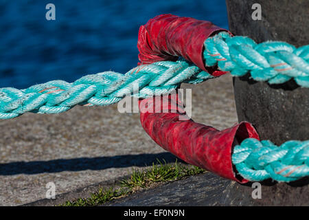 Bollard with rope in a port. - Stock Photo