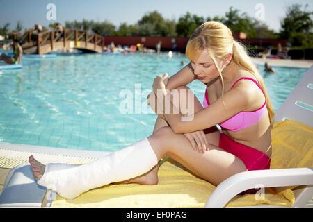 Frau Jung Gipsbein Pool Sommer Urlaub Holiday Unfall Verletzung Beinbruch Bein Gips Behinderung Gehbehinderung Schicksal - Stock Photo