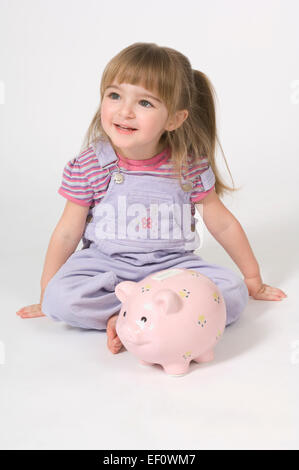 Young girl sitting in front of a piggy bank - Stock Photo