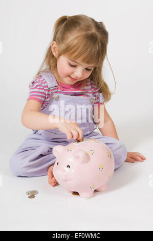 Young girl putting coins in a piggy bank - Stock Photo
