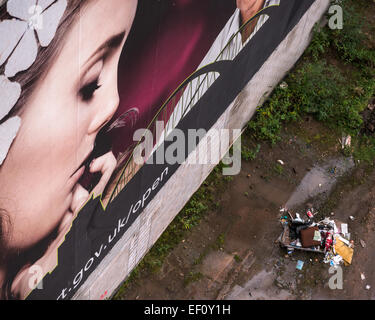An instance of fly tipping next to a large banner depicting a beautiful lady looking down at the waste. - Stock Photo