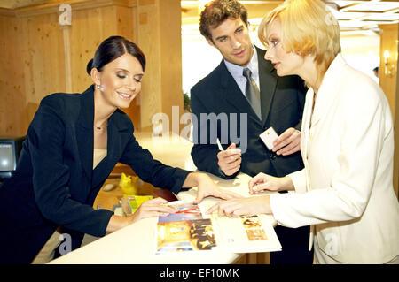 Hotel Rezeption Paar Jung Einchecken Laecheln Hotelrezeption Theke Empfang Frau Angestellte Rezeptionistin Hotelgaeste - Stock Photo