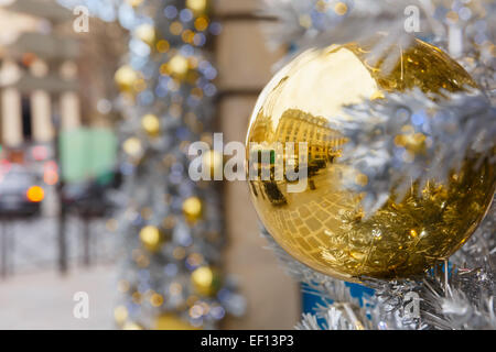 Golden shiny ball on Christmas decorated street in Paris, France - Stock Photo