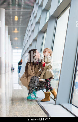 Mother and little daughter looking out the window at airport terminal - Stock Photo