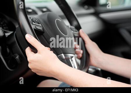 woman hands holding steering wheel in luxury car - Stock Photo