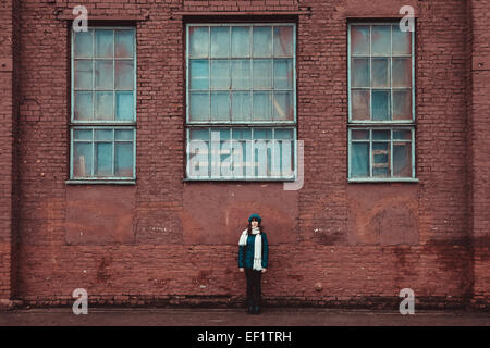 young girl standing near a brick wall - Stock Photo